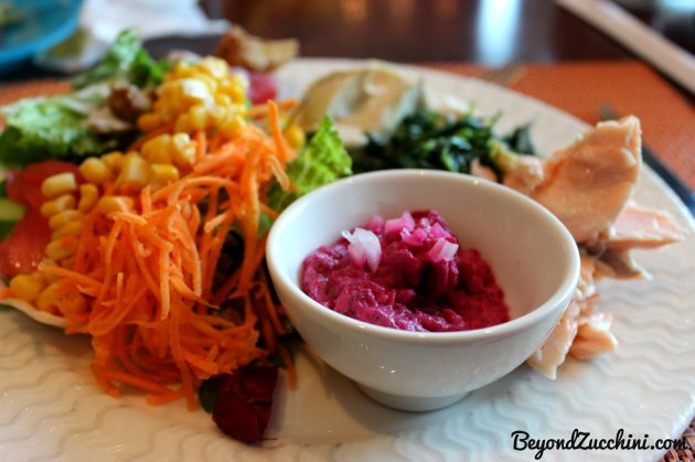 Healthy options at Al Bustan Rotana's brunch, including: beetroot-tahini puree with onions, hot-smoked salmon, sauteed spinach with onions and garlic, hummus, and a colorful mixed salad.